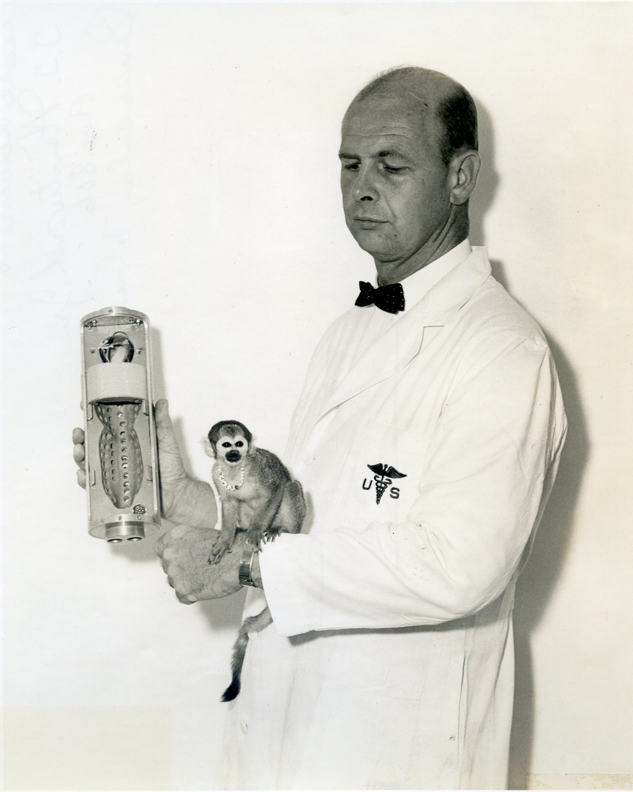 Miss Baker Dr. Donald E. Stullken holding space capsule that monkey Baker made her space trip in;
